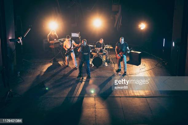 rock and roll band performing hard rock music on stage - rock band stock pictures, royalty-free photos & images