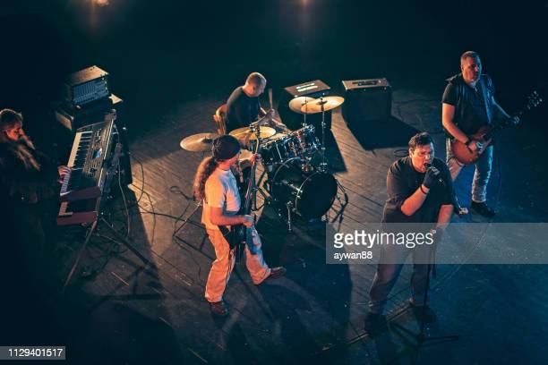 rock and roll band performing hard rock music on stage - heavy metal stock photos and pictures
