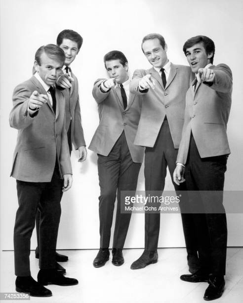 "Rock and roll band ""The Beach Boys"" point at the camera as they pose for a portrait in 1964. Al Jardine, Brian Wilson, Carl Wilson, Mike Love, Dennis..."