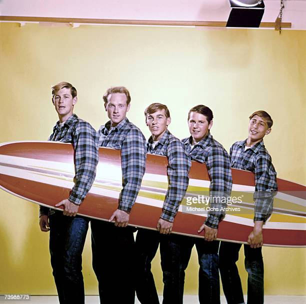 "Rock and roll band ""The Beach Boys"" pose for a portrait with a surfboard in August 1962 in Los Angeles, California. Brian Wilson, Mike Love, Dennis..."