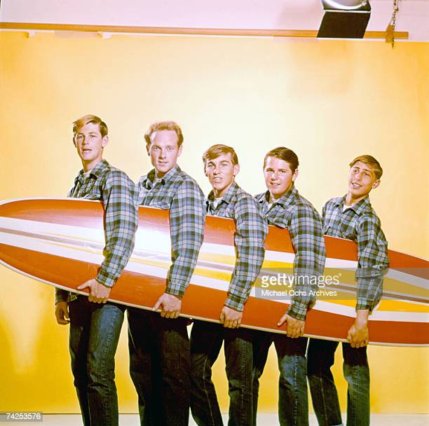 """Rock and roll band """"The Beach Boys"""" pose for a portrait with a surfboard in August 1962 in Los Angeles, California. Brian Wilson, Mike Love, Dennis..."""