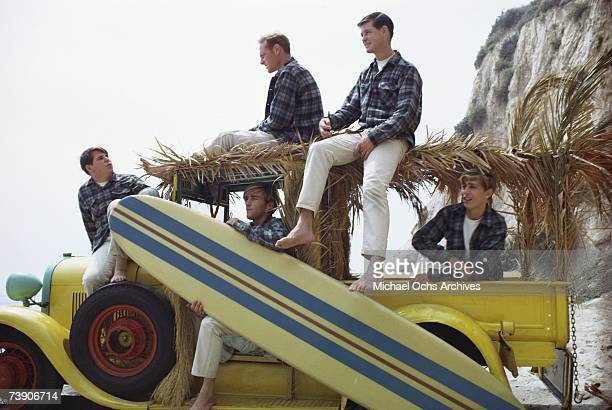 """Rock and roll band The Beach Boys pose for a portrait with a vintage """"Woody"""" station wagon in August 1962 in Los Angeles, California. Carl Wilson,..."""