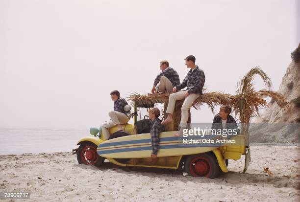 """Rock and roll band """"The Beach Boys"""" pose for a portrait with a vintage station wagon in August 1962 in Los Angeles, California. Carl Wilson, Mike..."""