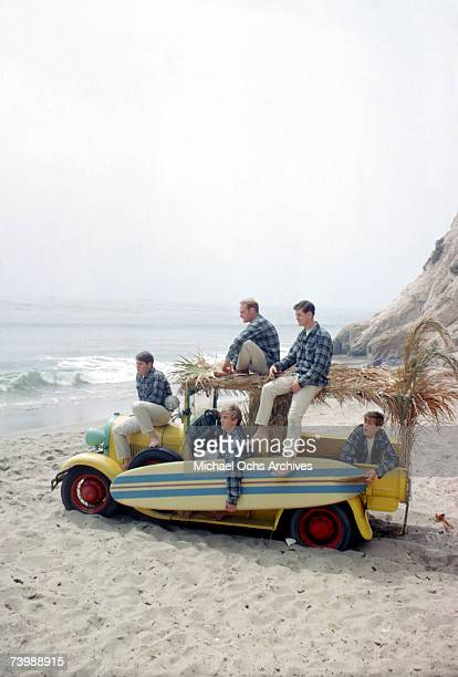 "Rock and roll band ""The Beach Boys"" pose for a portrait with a vintage station wagon in August 1962 in Los Angeles, California. Carl Wilson, Mike..."