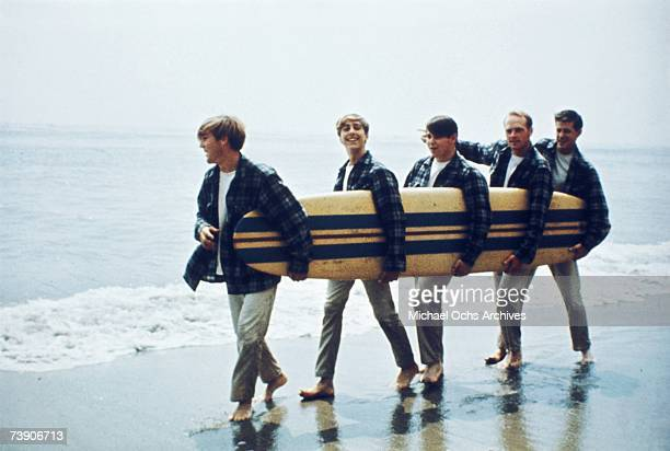 Rock and roll band The Beach Boys walk along the beach holding a surfboard for a portrait session in August 1962 in Los Angeles, California. Dennis...