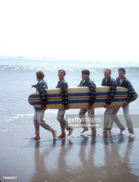 """Rock and roll band """"The Beach Boys"""" walk along the beach holding a surfboard for a portrait session in August 1962 in Los Angeles, California. Dennis..."""