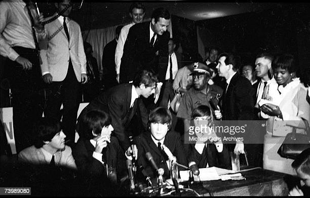 Rock and roll band 'The Beatles' hold court at a press conference as their manager Brian Epstein leans in to advise them in 1964 Paul McCartney...