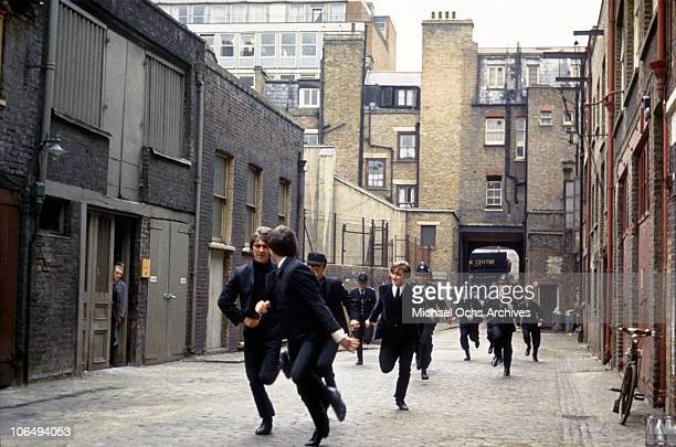 Rock and roll band 'The Beatles' run from the police in a still from their movie 'A Hard Day's Night' which was released in 1964 George Harrison Paul...