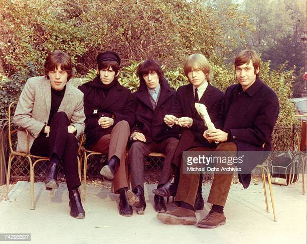 Rock and roll band 'The Rolling Stones' pose for a portrait sitting on chairs on a patio in 1964 Mick Jagger Keith Richards Bill Wyman Brian Jones...