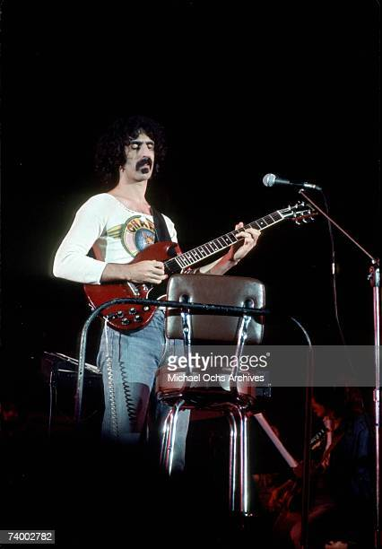 Rock and roll guitarist Frank Zappa performs onstage wearing a 'Charp Hot Rats' tshirts in circa 1975 in Los Angeles California