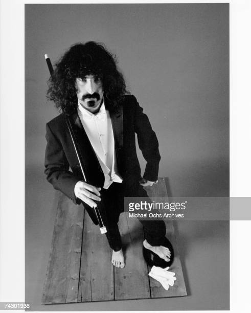 Rock and roll guitarist Frank Zappa poses for a portrait wearing a tuxedo with bare feet and white gloves on the floor in circa 1975