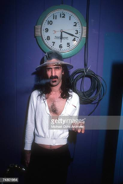 Rock and roll guitarist Frank Zappa poses for a portrait wearing a funny hat and smoking a cigarette as the clock behind him reads 618 in April 1979...