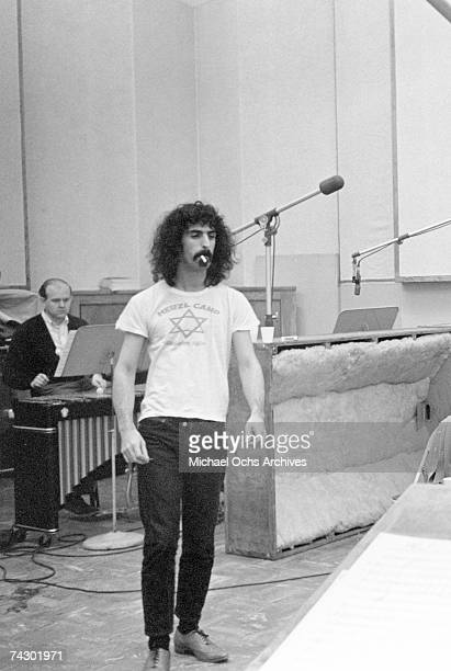 Rock and roll guitarist Frank Zappa walks through the recording studio wearing a 'Herzl Camp' tshirt smoking a cigarette in 1967