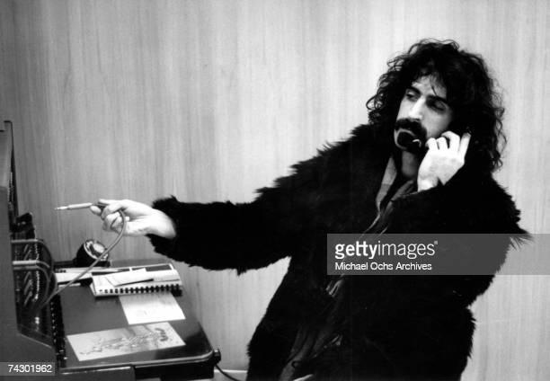 Rock and roll guitarist Frank Zappa wears a black fur coat as he operates a telephone switchboard and talks on the phone at Apostolic Studio Soho on...