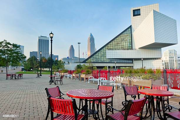 rock and roll hall of fame, brick patio, red furniture - rock and roll hall of fame cleveland stock photos and pictures
