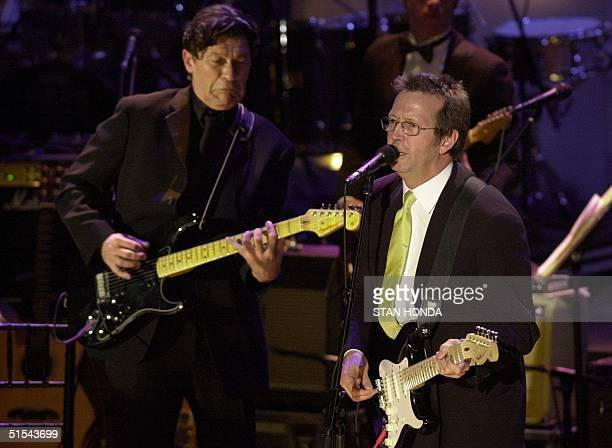 Rock and Roll Hall of Fame inductee Eric Clapton sings with guitarist Robbie Robertson during induction ceremonies 06 March 2000, at the...