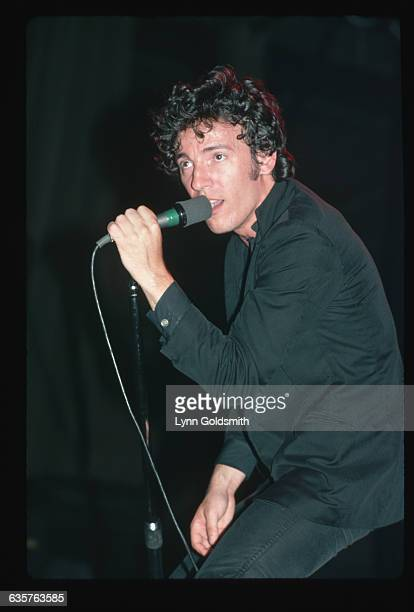 Rock and roll musician Bruce Springsteen leans into the microphone during an unidentified concert He is wearing a black sports jacket and tight black...