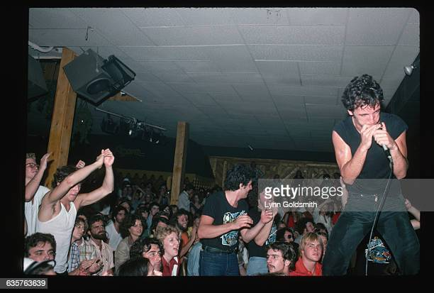 Rock and roll musician Bruce Springsteen plays the harmonica during an unidentified concert in a club His back is to the audience who are mostly...