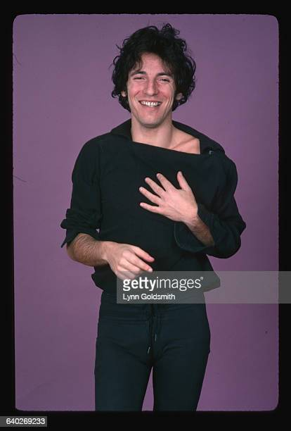 Rock and roll musician Bruce Springsteen smiles with his hand on his chest in this 3/4 length photo Springsteen is wearing a loose collar pull over...