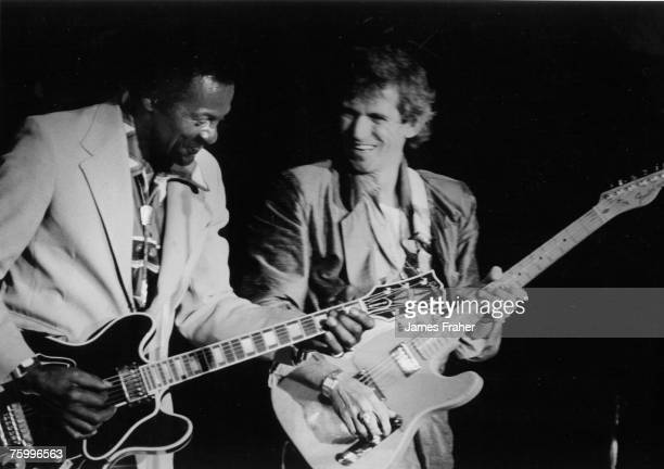 Rock and roll musician Chuck Berry performs onstage with his Gibson hollowbody electric guitar and guitarist Keith Richards of the rock and roll band...