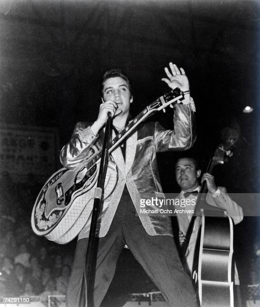Rock and roll musician Elvis Presley and his upright bass player Bill Black perform on stage in 1957 Elvis is wearing his gold lame Nudie Cohn...