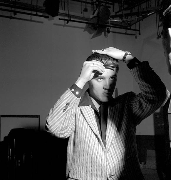 Rock and roll musician Elvis Presley combs his hair