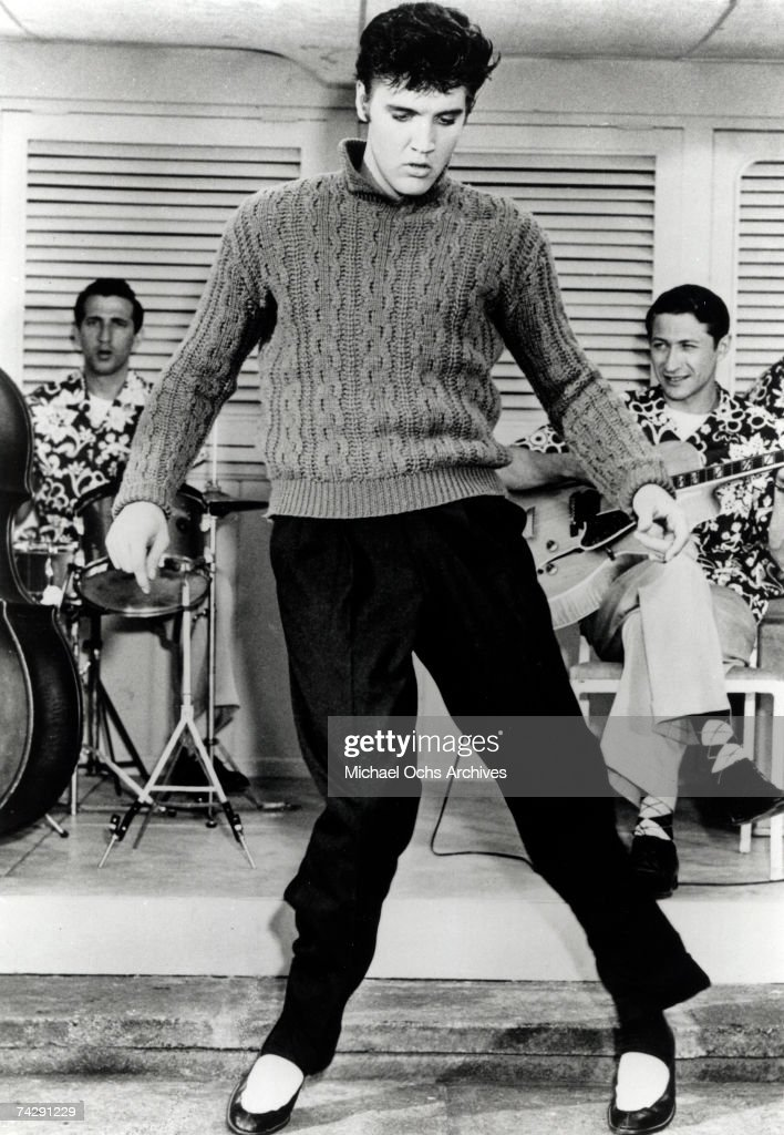 Rock and roll musician Elvis Presley dances in front of his band in a movie still from 1956.