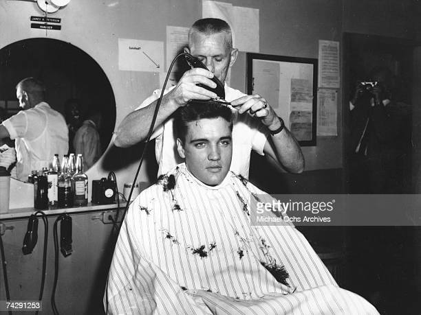 Rock and roll musician Elvis Presley gets his hair shorn off in preparation for his tour of duty in in the United States Army in 1959 in Germany....
