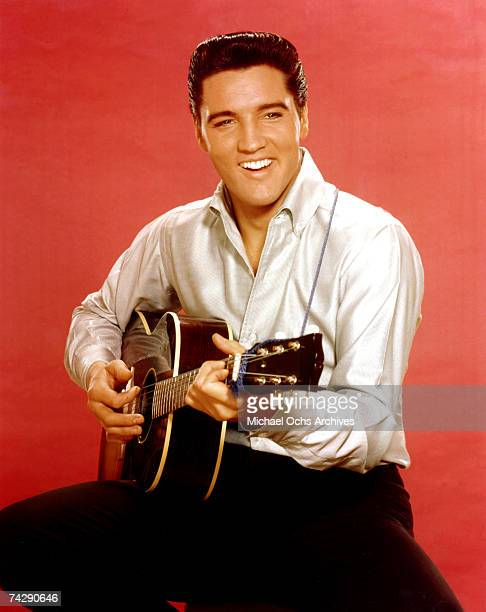 Rock and roll musician Elvis Presley strums an acoustic guitar while posing for a portrait in September 1962 in Culver City, California at MGM...