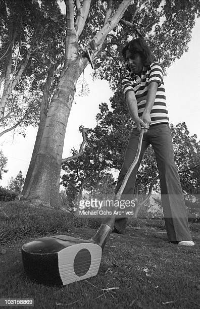 Rock and roll singer Alice Cooper prepares to take a swing with a golf club in circa 1977