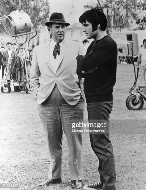 Rock and roll singer and actor Elvis Presley confers with Colonel Tom Parker on the set of one of his films