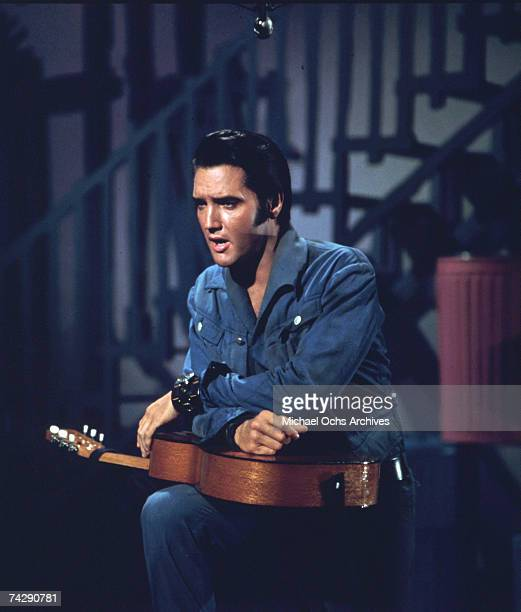 Rock and roll singer Elvis Presley holds an acoustic guitar in a movie still from circa 1964