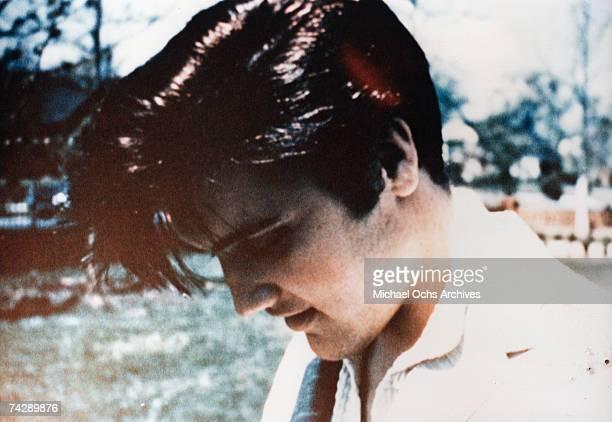 Rock and roll singer Elvis Presley looking down in 1955