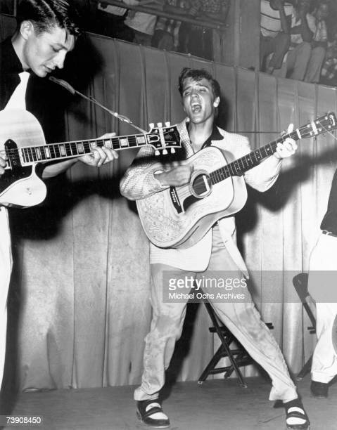 Rock and roll singer Elvis Presley performs on stage with his brand new Martin D28 acoustic guitar and Scotty Moore on the left on July 31 1955 at...