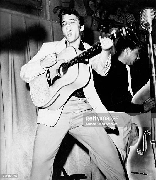 Rock and roll singer Elvis Presley performs on stage with his brand new Martin D-28 acoustic guitar on July 31, 1955 at Fort Homer Hesterly Armory in...