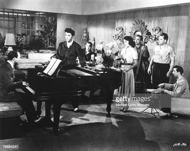 Rock and roll singer Elvis Presley performs on the set of his film 'Jailhouse Rock' with songwriter Mike Stoller Scotty Moore Judy Tyler Bill Black...