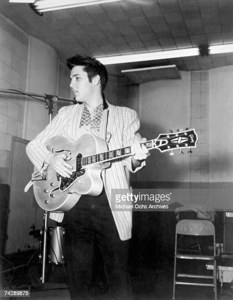 Rock and roll singer Elvis Presley playing a Gibson guitar in a recording studio in circa 1956 in Los Angeles California
