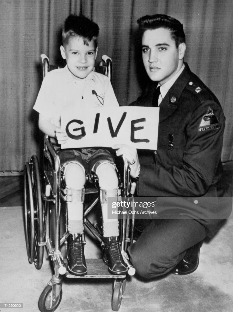 Rock and roll singer Elvis Presley poses for a photo with the March of Dimes poster child in January 1959 in Germany.
