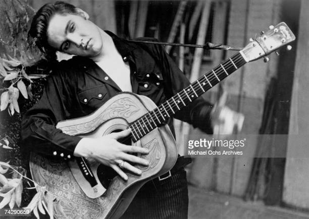 Rock and roll singer Elvis Presley poses for a portrait holding an acoustic guitar in 1956.