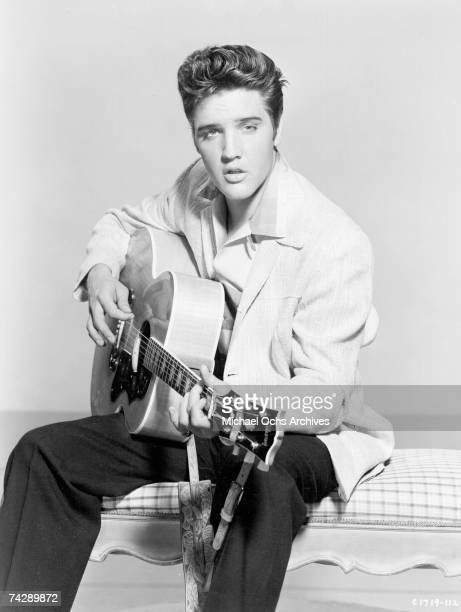 Rock and roll singer Elvis Presley poses for a portrait holding his acoustic guitar in circa 1957