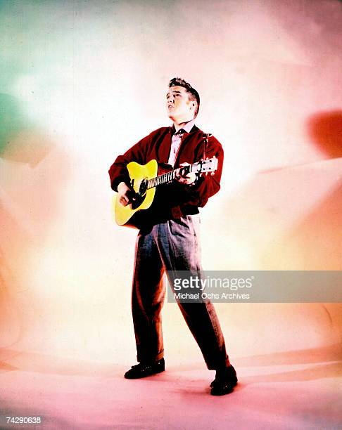 Rock and roll singer Elvis Presley poses for a portrait while playing his acoustic guitar in 1956.