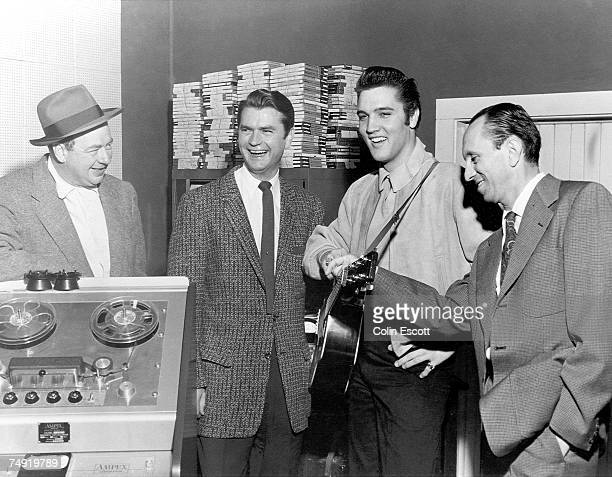 Rock and roll singer Elvis Presley poses with record producer Sam Phillips Leo Soroka and Robert Johnson at Sun Recording Studios in Memphis...