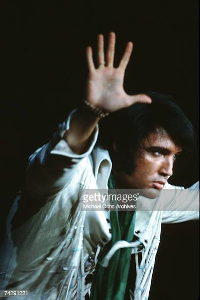 Rock and roll singer Elvis Presley raises his hands on stage in circa 1973
