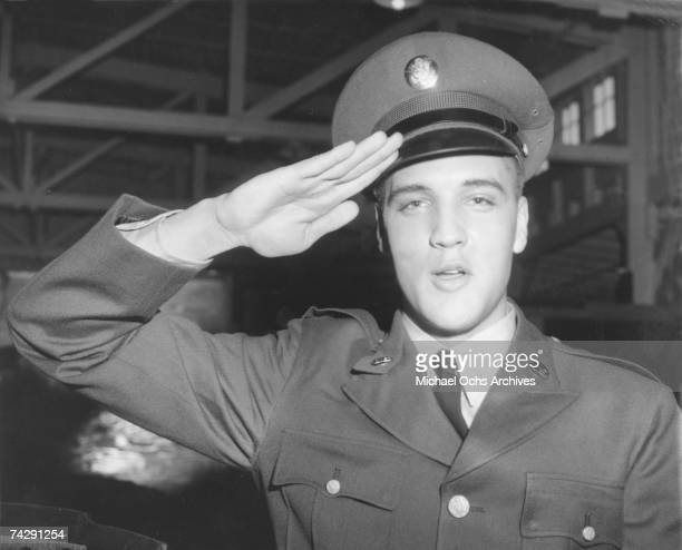 Rock and roll singer Elvis Presley salutes for a portrait during his tour of duty in Germany in February of 1959.