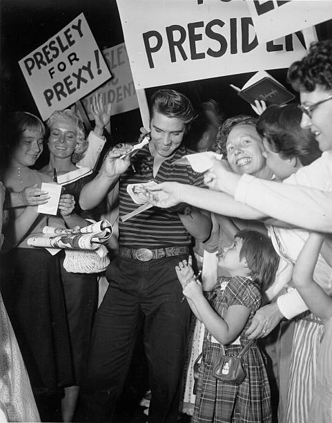 Rock and roll singer Elvis Presley signs autographs