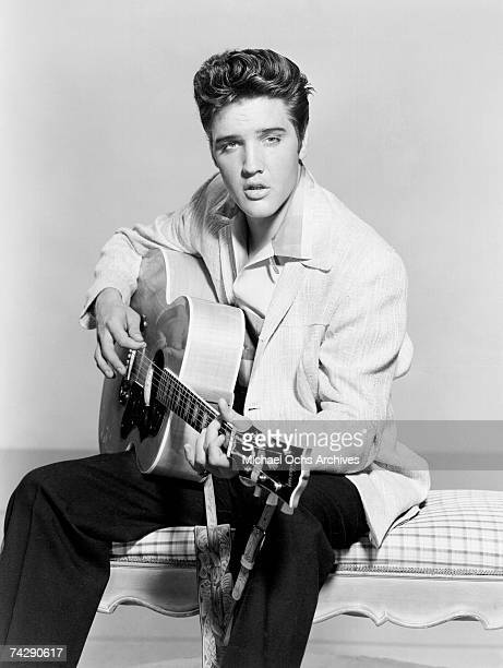 Rock and roll singer Elvis Presley strums his acoustic guitar in a portrait in 1956.