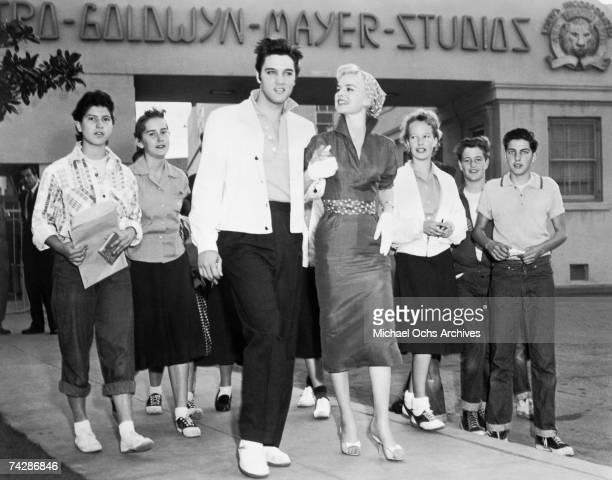 Rock and roll singer Elvis Presley with actress Barbara Lang and fans visits the MGM lot before starting work on the movie Jailhouse Rock in February...