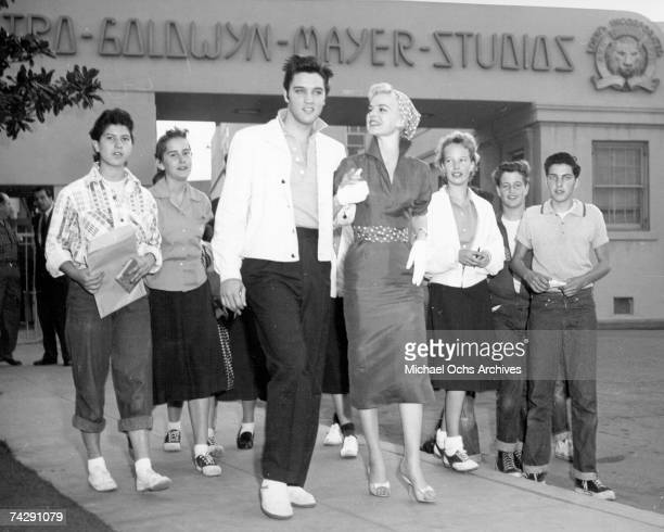 Rock and roll singer Elvis Presley with actress Barbara Lang and fans visits the MGM lot before starting work on the movie 'Jailhouse Rock' in...