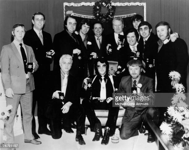 Rock and roll singer Elvis Presley with members of his entourage show off the badges they have just received from Sheriff Nixon at Graceland on...