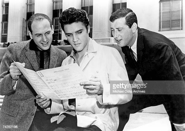 Rock and roll singer Elvis Presley with songwriters Leiber and Stoller looking over the sheet music for Jailhouse Rock at MetroGoldwynMayer Studios...